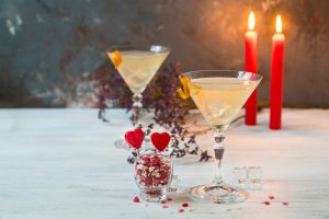 glasses with a cocktail and candles on a gray background. romantic candlelight dinner on Valentine's day