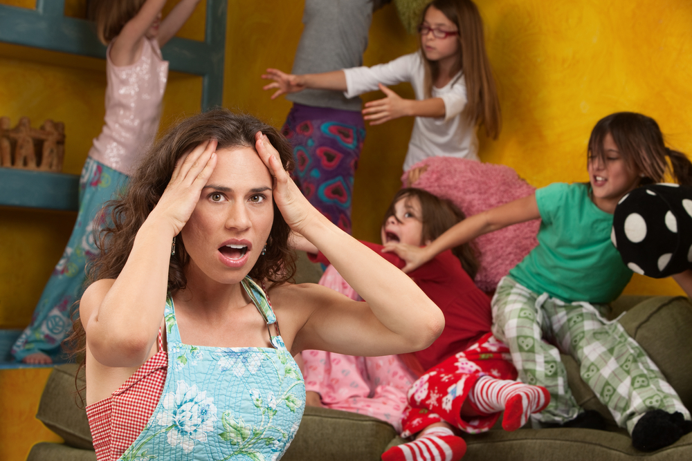 Upset mother with hands on head among mischievous little girls